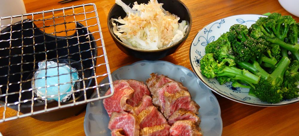 オニオンスライスとゆでたブロッコリー、とうがらし肉のたたき。一人用コンロ。