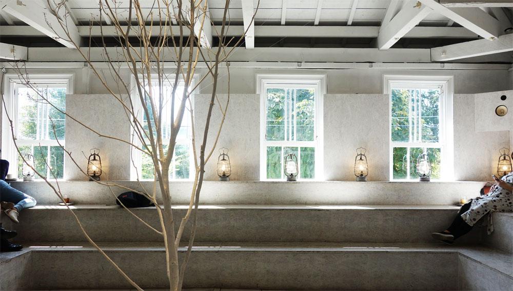 Walden Woods Kyoto (ウォールデン ウッズ キョウト)さんの二階の飲食スペース。真っ白に塗られた壁や梁が趣きある