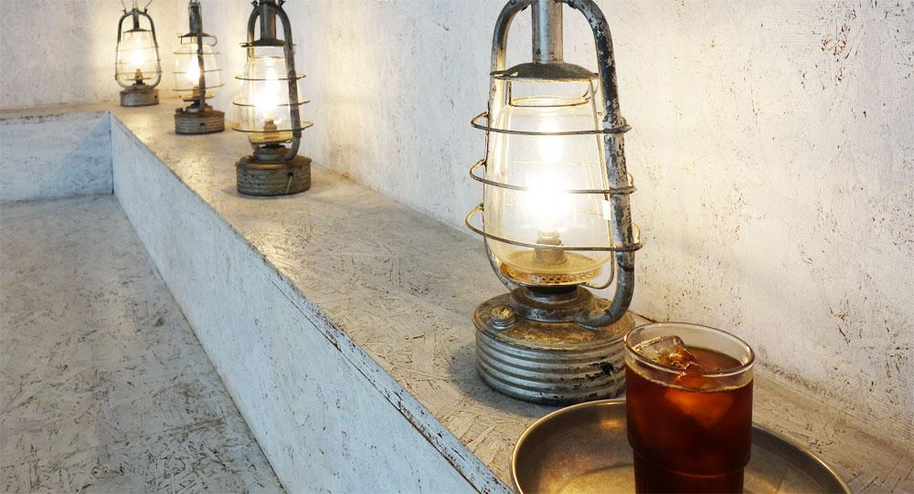 カフェ Walden Woods Kyoto (ウォールデン ウッズ キョウト)さんのアイスコーヒー。照明は穴があけてあって下に電線が通ってるみたい。なんだか船の照明のよう