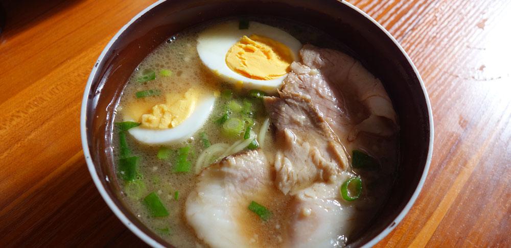 ますたにのラーメンにゆで卵と、ネギの小口切りを入れて、紅茶豚のスライス。