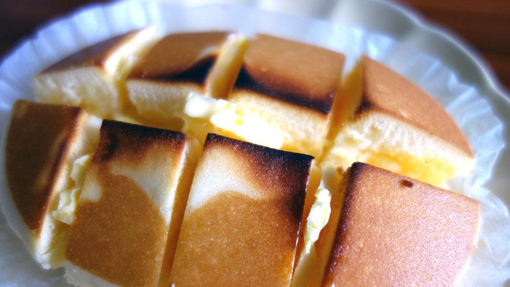 焼いた北海道チーズ蒸しケーキにカットしたバターをはさむ